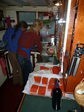 Photo: In a galley the size of a walk-in closet, Fern prepares three meals a day for nine passengers.  Miray is lending a hand.  Photo by Ben.