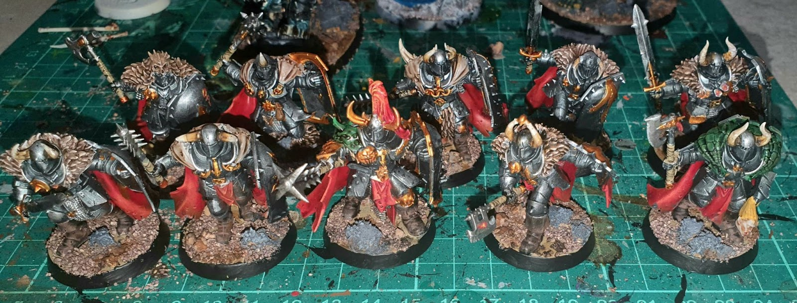 Chaos Warriors with the same gunmetal and gold armour and red cape colour.
