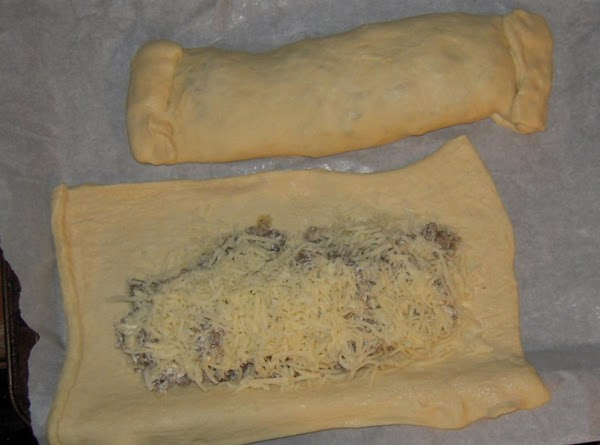Take one side of dough and stretch over meat mixture and do the same...