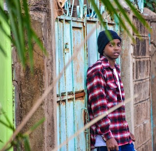 A photo of Kevin, a young man wearing a black beanie and red flannel shirt, leaning against a bright blue fence.