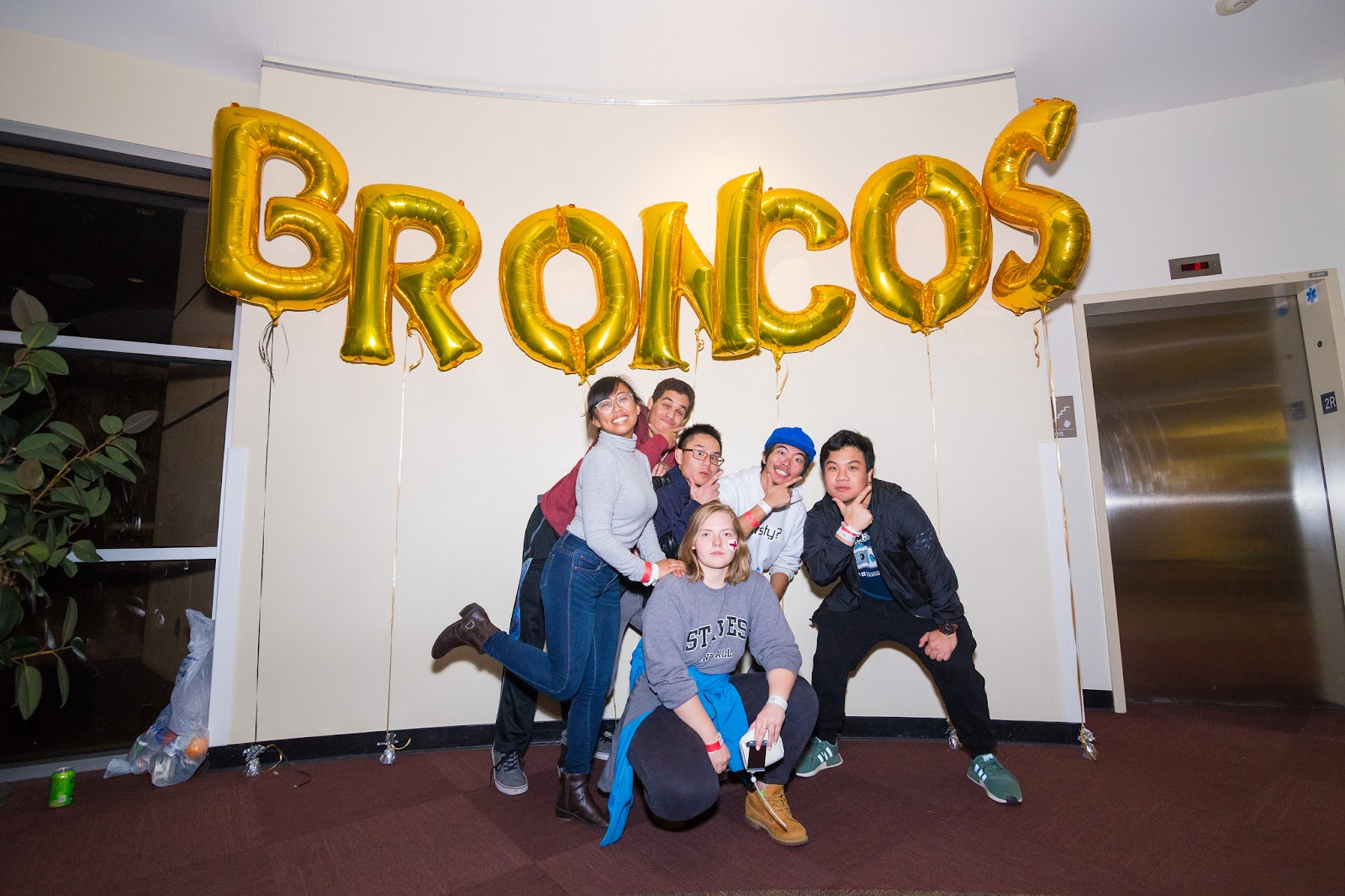 """Students posing under balloons that read """"BRONCOS."""""""