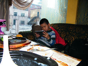 Photo: family annual dined out in U.B.C coffee in Qiqihar commercial zone, celebrating lunar spring festival. son enjoyed steak there with his proud dad, benzrad, for the moment rich and leisure. here son played video game on his pad before served.