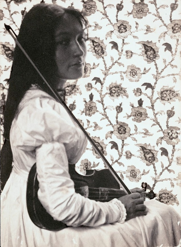 """Zitkala-Sa"" wearing a white long-sleeved dress and holding violin and bow, floral wallpaper in background. Credit: Gertrude Kasebier (Smithsonian Institution)"