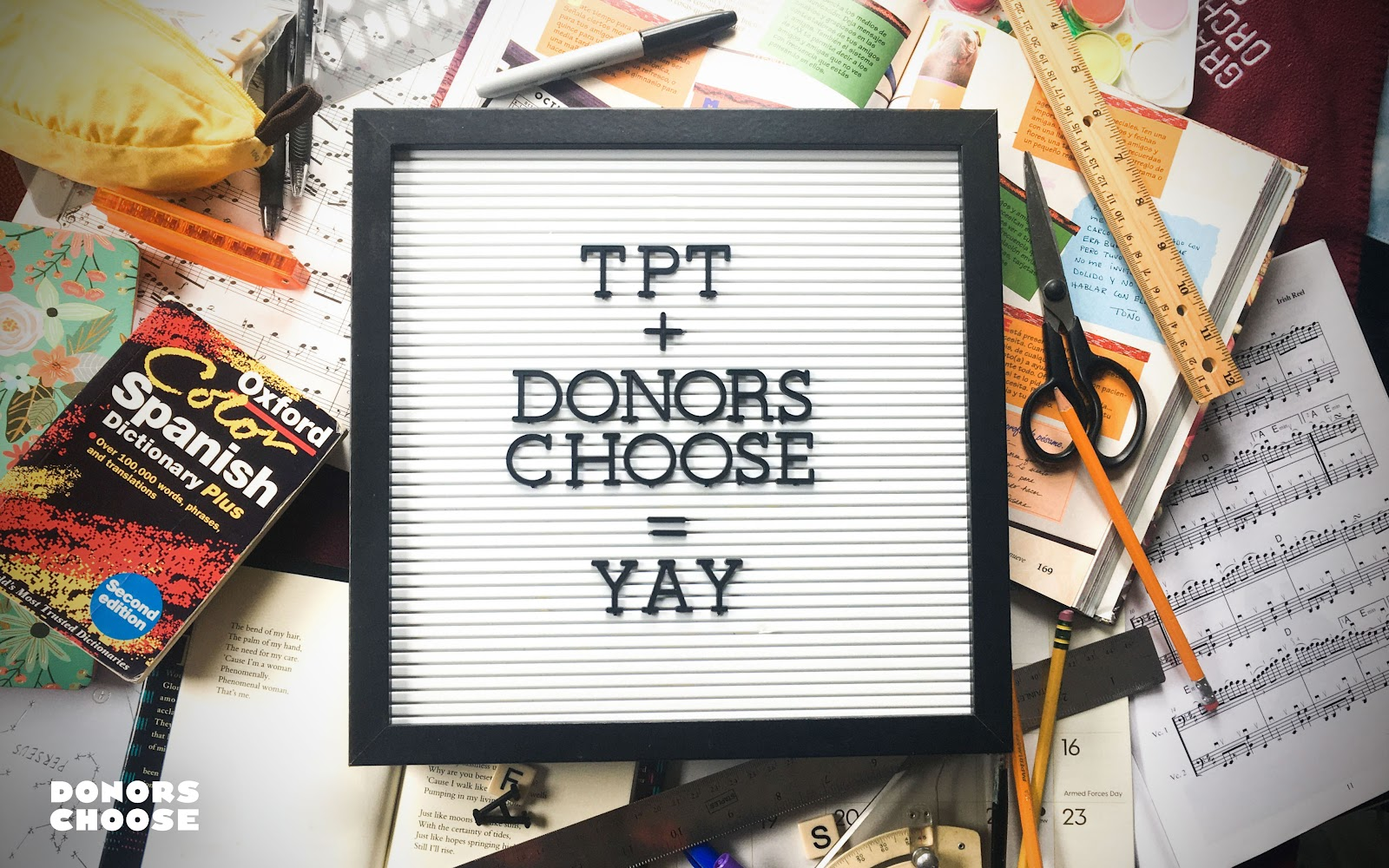 "A sign that reads ""TPT+ DONORSCHOOSE = YAY"" on top of a pile of colorful school supplies"