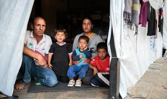 Field workers pose with three refugee children in the doorway of a temporary shelter.