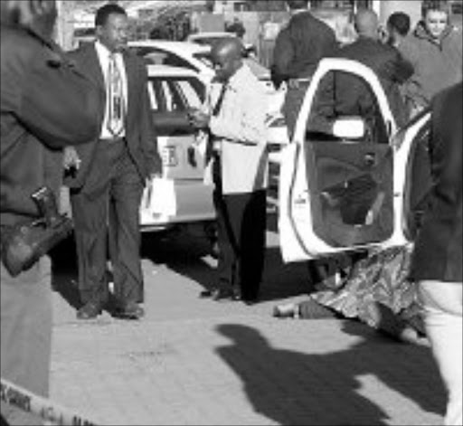 CRIME VICTIM: The body of Sergeant Moeketsi Lekojane is covered with a blanket after he was shot dead in Zola, Soweto, yesterday. Pic. Lucky Nxumalo. 29/08/07. © Sowetan.
