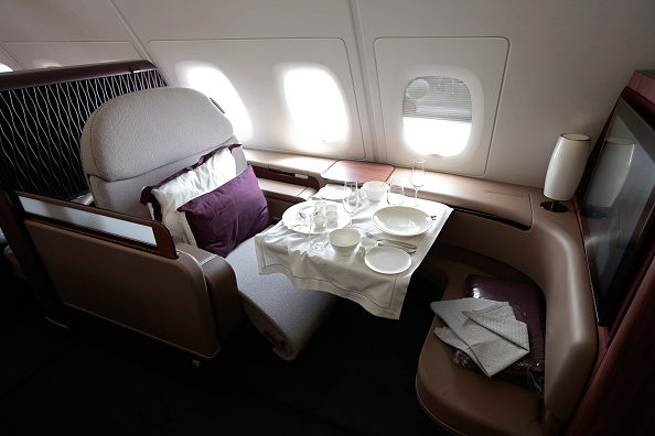 A dining set sits on the table of a First Class passenger booth inside an Airbus SAS A380 aircraft, operated by Qatar Airways.
