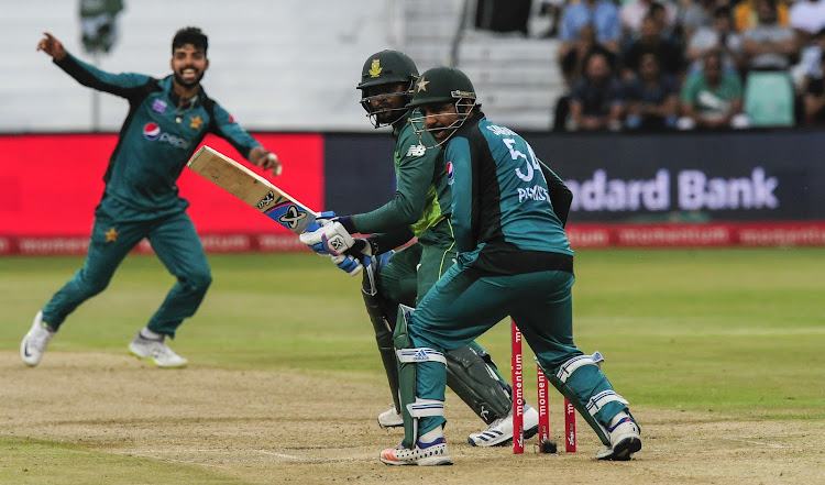 Andile Phehlukwayo of South Africa watches the ball go past out of reach of Pakistan wicketkeeper/batsman and captain Sarfraz Ahmed (c) during the International One Day Series game at Kingsmead Stadium in Durban on January 22 2019.