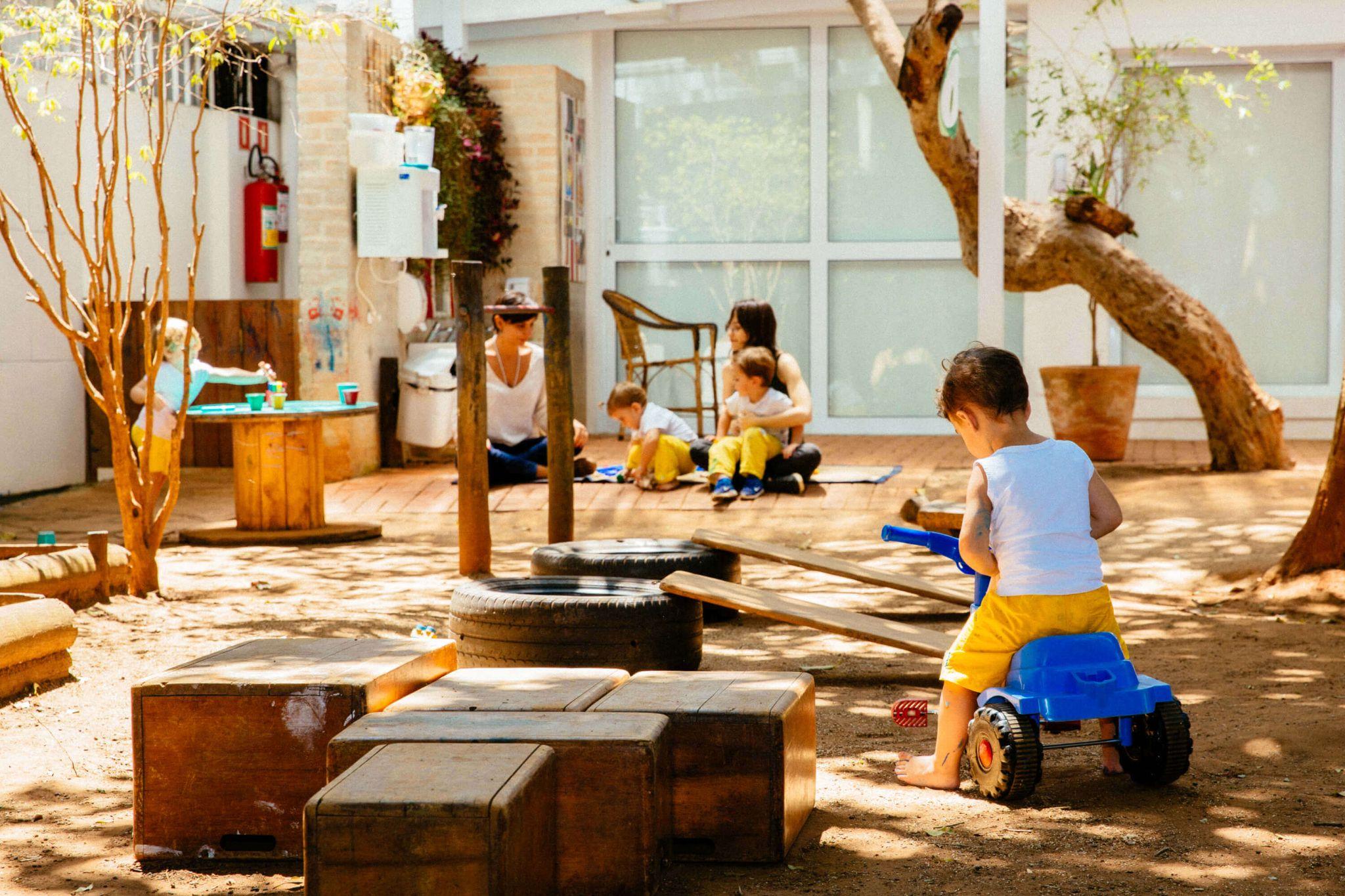 A imagem mostra um grupo de crianças brincando em um quintal.