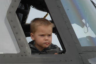 Photo: A child looks out from the pilots seat of a CH-47 Chinook helicopter.