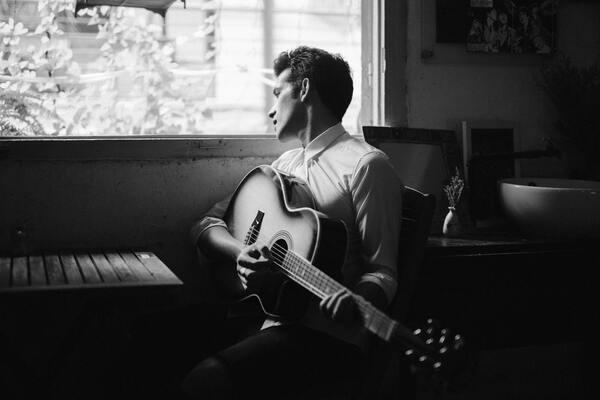 Foto de um homem sentado tocando um violão