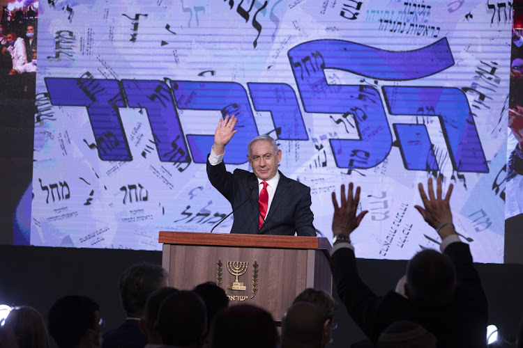 Benjamin Netanyahu, Israel's prime minister and the leader of the Likud party, waves to his supporters on stage during a party event in Jerusalem, Israel, on Wednesday, March 24, 2021. Israel's fourth election in two years might not resolve the country's damaging political impasse, with neither Netanyahu nor his opponents having a secure path to form a coalition government, exit polls show. Picture: BLOOMBERG/KOBI WOLF