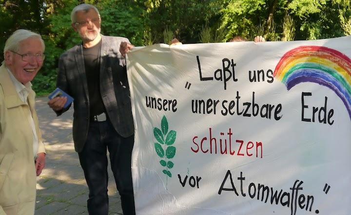 Zwei Demonstranten, Transparent: «Lasst uns unsere unersetzbare Erde schützen vor Atomwaffen».