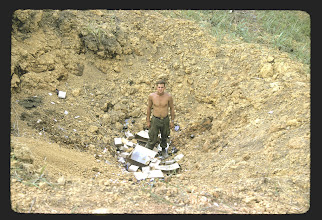 Photo: Bennie Koon in crater on LZ Peanuts also serving as a garbage dump.