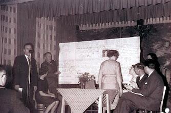 Photo: V.C.J.C bestaat 25 jaar, oktober 1961 De oud leden biedt het bestuur van de jubilerende vereniging een postwissel aan. Met de rug naar ons toe is Giny Jansen-Lanjouw, zij was toen voorzitster. Harm Zandvoort staat achter de microfoon., daarnaast zit Roelie Sloots en Egbert Bruining. rechts Dominee S. de Jong en Roelof Vedder.