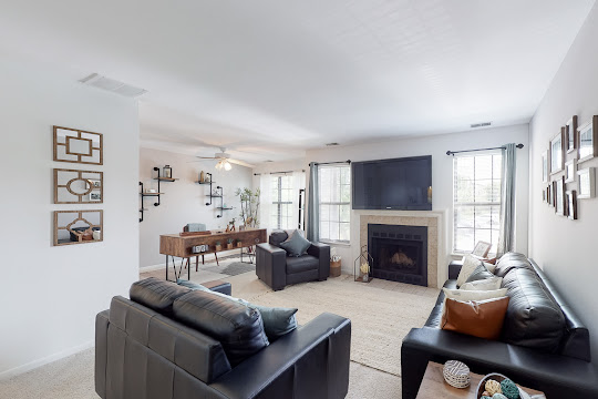 Spacious living area with a cozy fireplace and windows for plenty of natural lighting