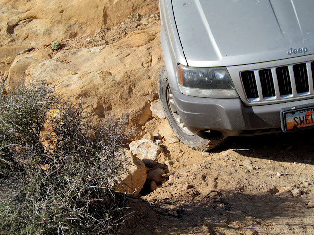 Sand and rocks sloughing off the road