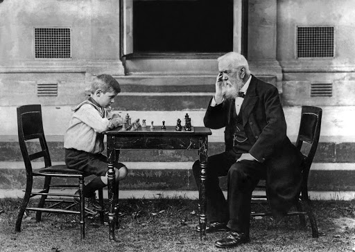 Walter Wisby, aged eight, playing a game of chess with T Whiltard, aged 91, in Cheltenham in August 1913.