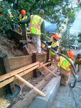 Photo: San Francisco Department of Public Works employees pump concrete through hose into post-holes that are several feet deep to cement erosion-control barrier posts into place on the final sections of terraced erosion-control barriers on October 10, 2013. The area is the last on the Hidden Garden Steps site (16th Avenue, between Kirkham and Lawton streets in San Francisco's Inner Sunset District) in need of attention before the Hidden Garden Steps 148-step ceramic-tile mosaic designed and created by artists Aileen Barr and Colette Crutcher is installed. For more information about this volunteer-driven community-based project supported by the San Francisco Parks Alliance, the San Francisco Department of Public Works Street Parks Program, and hundreds of individual donors, please visit our website at http://hiddengardensteps.org.