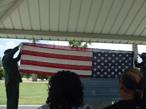 Photo: the guards begin to fold the flag from his casket