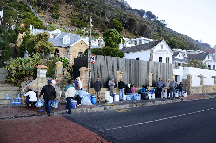 Residents queue at St James in Cape Town to collect water running down from the mountain. File photo