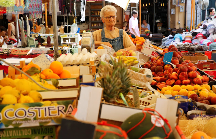 A greengrocer at her stand in the Campo dei Fiori market in downtown Rome Italy.