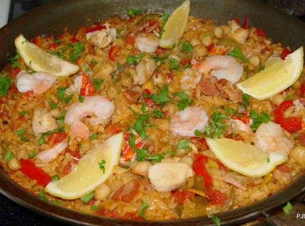 Arrange the scallops, chicken and shrimp around the surface of the paella, and add...