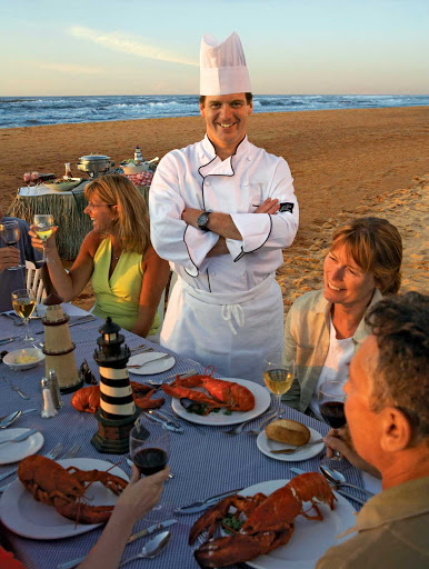 A chef  and guests at a lobster dinner on the beach on Prince Edward Island, Canada.