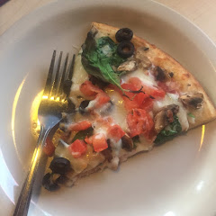 Gf pizza with tomato, spinach, mushrooms and olives.