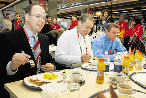 Jacques Rogge, president of the IOC, centre, eats next to Prince Albert of Monaco, left, and IOC member Sergei Bubka at the athletes' Olympic village during the Turin 2006 Winter Olympics. The canteen at this year's Games is said to be one of the best ever Picture: GALLO IMAGES