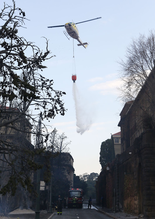 A helicopter water bombs the fire near the Jagger Library at the University of Cape Town.