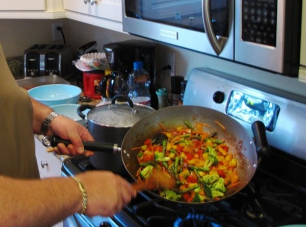Heat 2tbs veg oil in wok or lg skillet, add garlic, ginger and red...