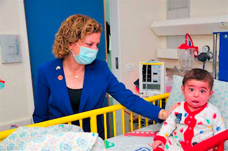 Photo: During her tour of the Department of Pediatric Hematology and Oncology at Hadassah Medical Center-Ein Kerem, Rep. Debbie Wasserman Schultz (D-FL) donned protective covering to visit one-year-old Alma Jaradat from Jenin, who was hospitalized in an isolation unit before undergoing bone marrow transplantation.