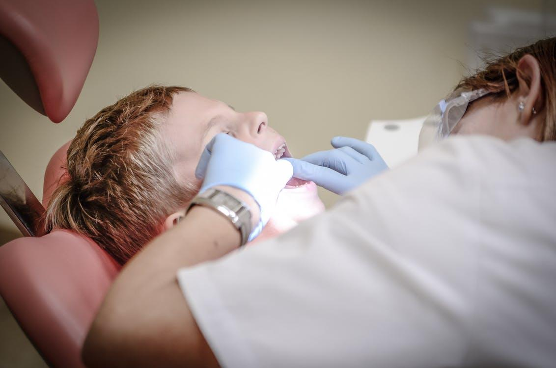 Dentist Woman Wearing White Gloves and White Scrubsuit Checking Boy's Teeth