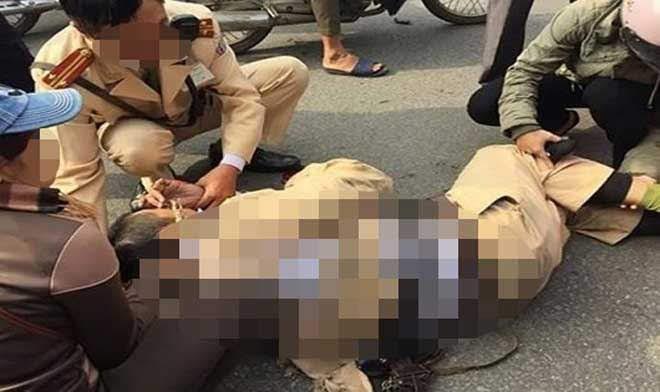 2 thượng úy công an đi xe máy không may va quẹt với dải phân cách bê tông trên đường khiến cả xe và người té xuống đường.