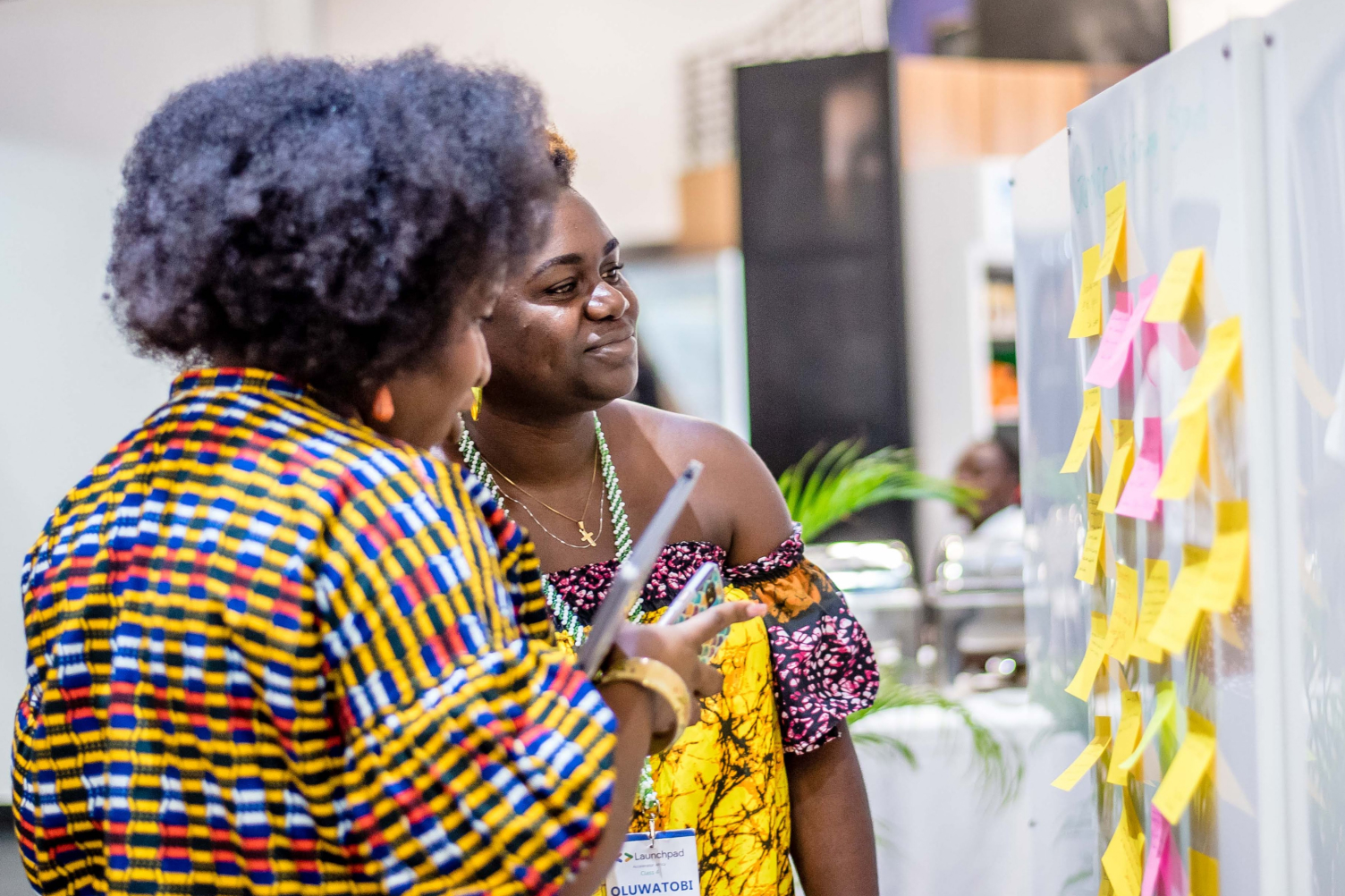Two women working with post-it notes on a whiteboard, smiling