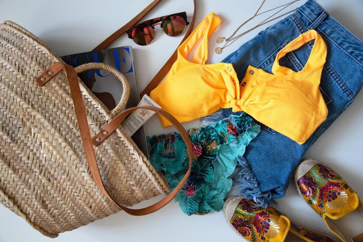 Una borsa di paglia, un costume, degli occhiali da sole, degli shorts e delle ciabatte da mare disposte su una superficie bianca