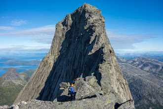 "Photo: The peak of the landmark mountain Stetind in Nordland, Norway, is a popular destination for hikers and climbers. The normal route is a hiking trip until one reaches the lower Halls Fortopp, but the traverse from here up to the main peak, from which the photo is taken, requires belaying, and a short climb via the fingertip traverse to pass a rock called ""Mysosten"" (grade 4). A more difficult but very popular route is via the South Pillar, consisting of 14 rope lengths."