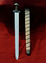 Photo: The main object here is the Viking Sword from a child's grave in Balnakeil, Durness, on the North coast of Scotland made by Tim Noyes. However, the remains of a scabbard were present too and replicated here. The last 20cm or so was missing as it protruded from the now exposed grave. The scabbard is made of oak lathes - one side pocketed and the second side glued over the blade, then bound with linen and finally a spiral wound linen taped glued over that. There was no evidence of any form of hanger or baldric. The scabbard has a number of parallels - Sutton Hoo for example and a fresco from the Oratory of St. Benedict in Rome. For such a fine example of a sword, sadly the hilt was seemingly wrapped in nothing more elegant than string. The scabbard is waterproof and entirely organic in its component parts and can be slung with a knotted leather baldric. The sword is fairly short and was broken in the scabbard with the lowest piece missing - about 600mm overall length.