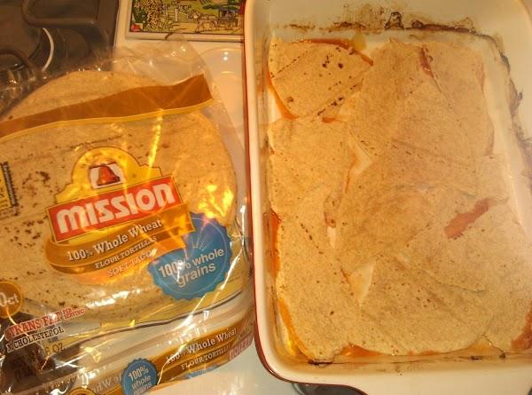 Tear up tortillas; add to baking pan.