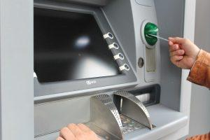A person placing a card in an ATM