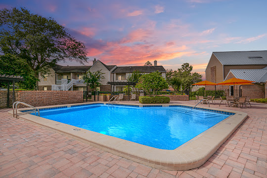 Swimming pool with picnic tables, lush landscaping, and apartment buildings in the background at dusk