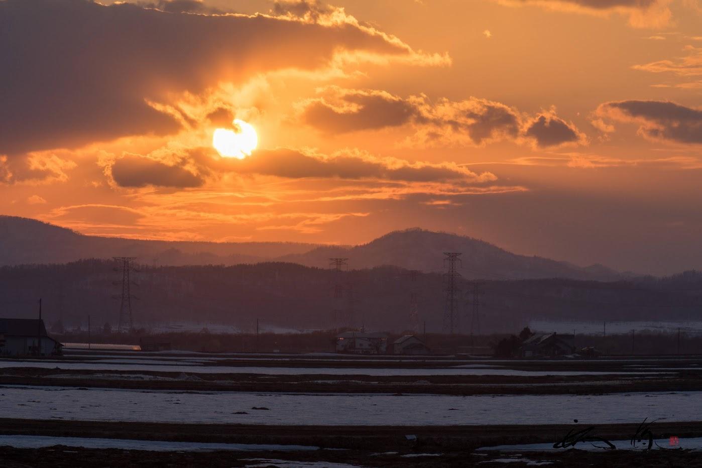 灰色の雲に包まれた夕陽