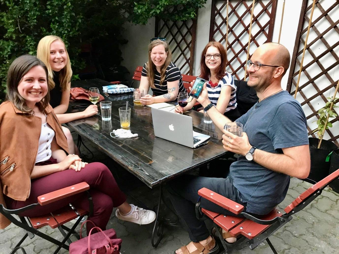 A group of people sitting around a table outside  Description automatically generated