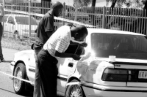20091022 BMA  Nine suspects have been arrested in connection with double robberies at a Nedbank and a jewelery store at the Menlyn Retail Park in eastern Pretoria. Seen here are police dusting the car for fingerprints from the to getaway car. PIC: BAFANA MAHLANGU. 22/10/2009. © SOWETAN