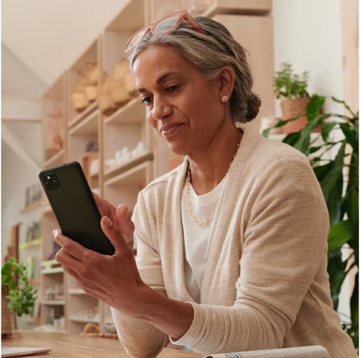 An image of a female small business owner looking at the features on her Google phone for work.