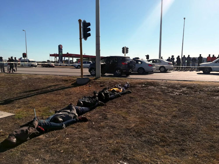 The arrested suspects lie on the ground after their vehicle was pulled off the road