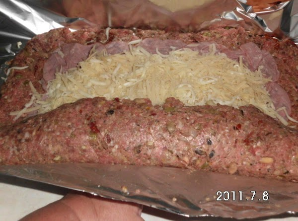 """Using foil as """"rolling tool"""" start rolling meat mixture up over cheese.  Seal..."""