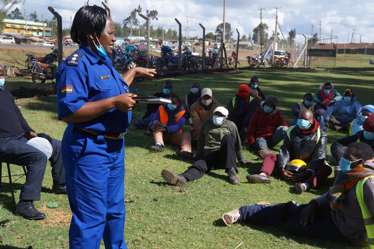 Lari deputy traffic police commander Lydia Jeruto with boda boda riders at Uplands on Tuesday.