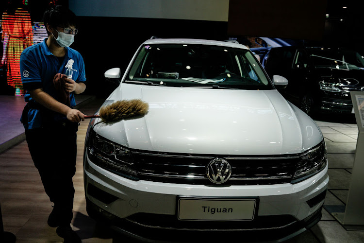 A staff member wears a protective mask while cleaning a Volkswagen booth at the 18th Central China International Auto Show on August 13 2020 in Wuhan, China.